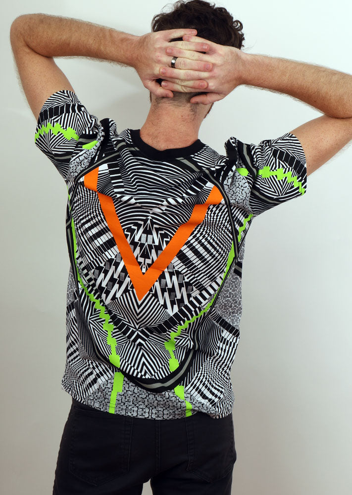Back view of a man with hands behind his head, showing off repeated graphic of back of tshirt in white black orange and lime green