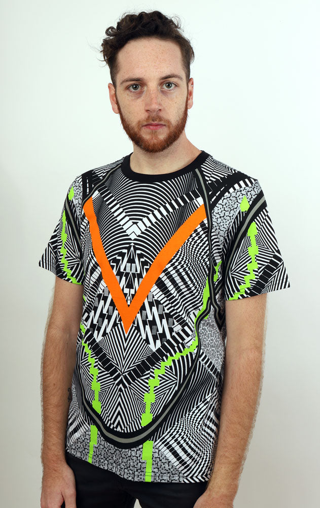 Man stares into camera wearing super graphic black and white Tshirt with orange and lime green accents