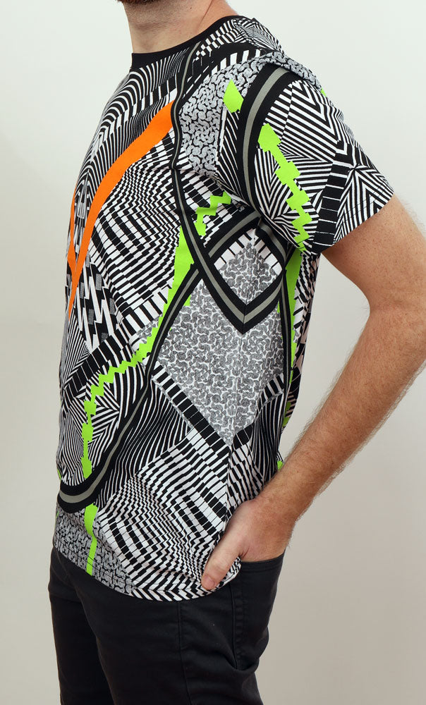 Close up, side view of man's body with hand in back pocket, wearing a very graphic white and black tshirt with orange and lime green accents