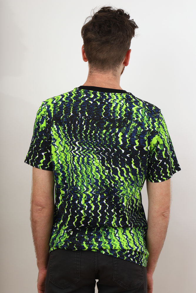 Back view of man in WHITE CRYPTO tshirt, which is not white but blues and lime greens matrix style pattern