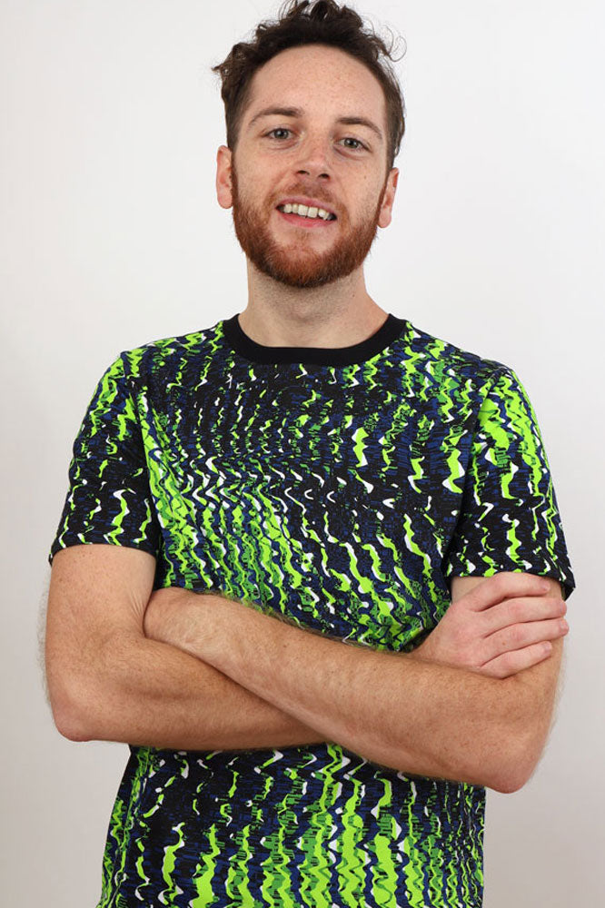 Man smiles at camera in a very graphic blues and greens tshirt, matrix style pattern on a short sleeve tshirt.