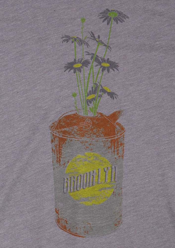 CLOSE UP OF THE DAISY CAN WOMEN'S T-SHIRT GRAPHIC RUSTY CAN WITH BROOKLYN WRITING ON IT, HOLDING SOME GREY DAISIES