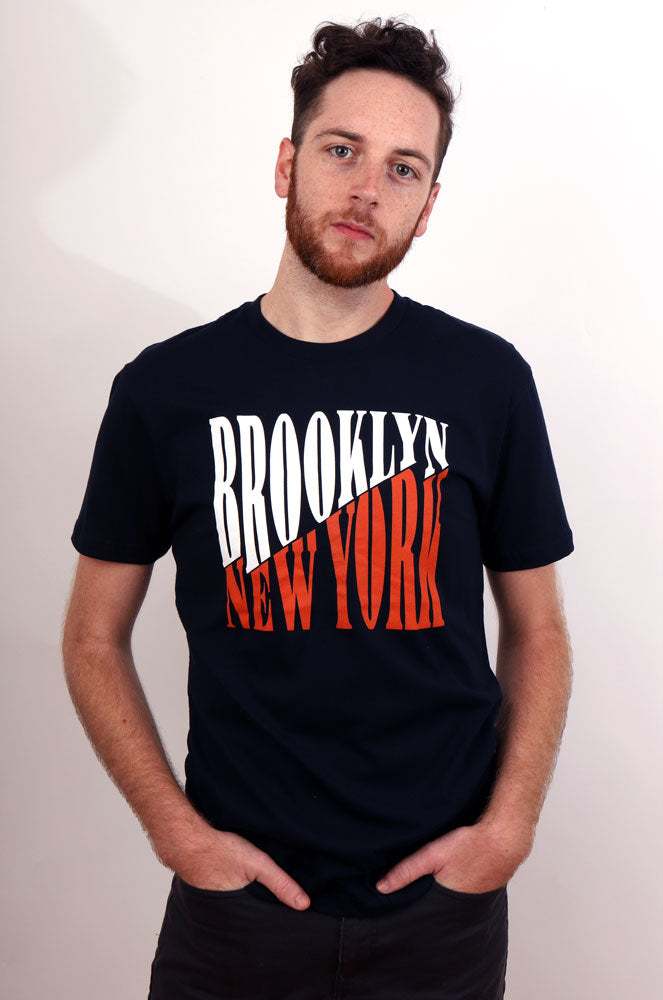 Man with hands in pockets looks at the camera in a studio setting, wearing a navy graphic tshirt that have brooklyn in white , and new york in orange, off setting eachother diagonal.