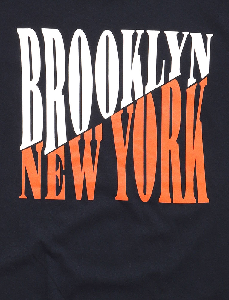 DETAIL OF NAVY SHIRT WITH BROOKLYN IN WHITE AND NEW YORK IN ORANGE ON A DIAGONAL