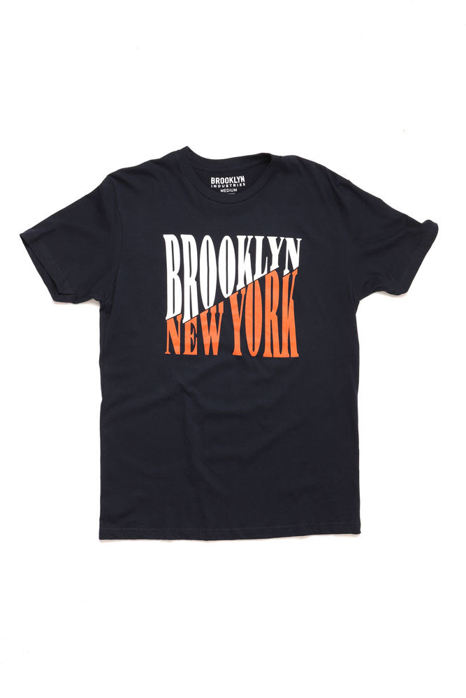 FLAT LAY OF NAVY SHIRT WITH BROOKLYN IN WHITE AND NEW YORK IN ORANGE ON A DIAGONAL