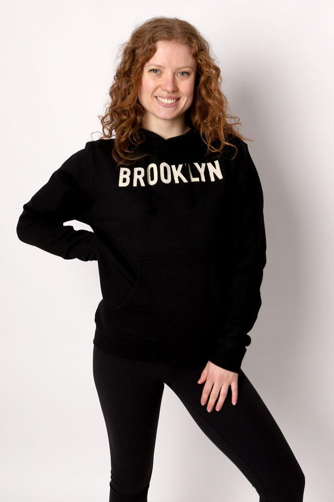 Women smiles with hand on hip, in black leggings and black hooded felt applique sweatshirt.