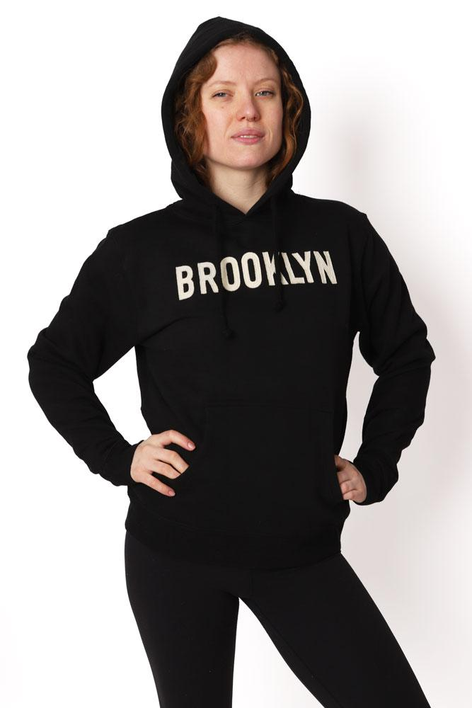 Women wears hood up with hands on hips. Black hoodie with cream lettering