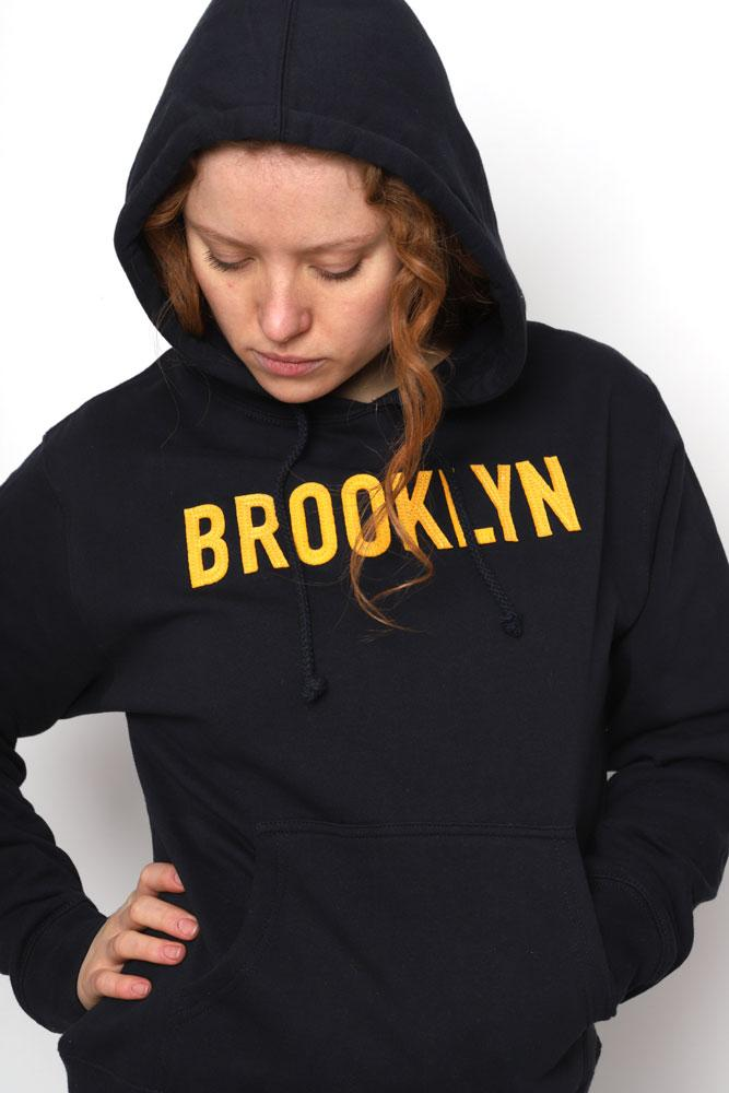 Women looks down in navy hooded sweatshirt with yellow applique BROOKLYN lettering.