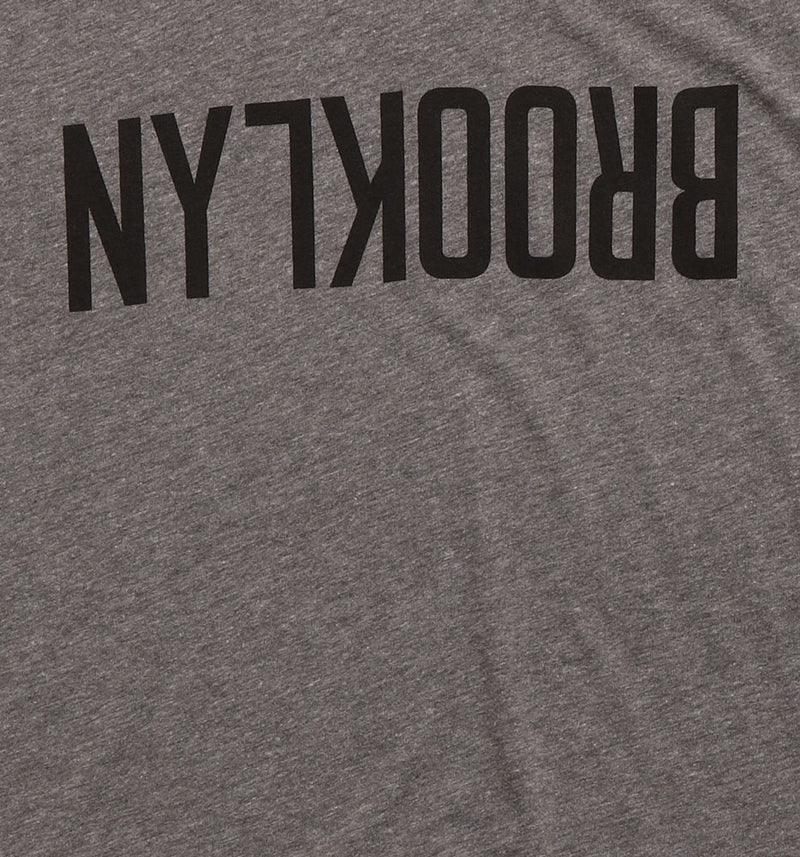 DETAIL OF BLACK BROOKLYN TEXT UPSIDE DOWN ON HEATHER TSHIRT