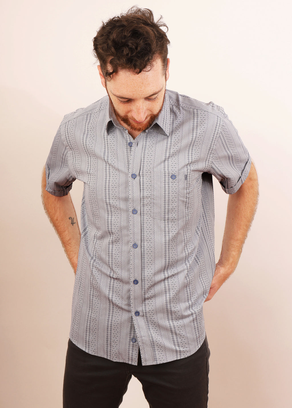 MAN WITH HANDS BEHIND BACK LOOKS DOWN IN GREY MIXED GRADO SHIRT