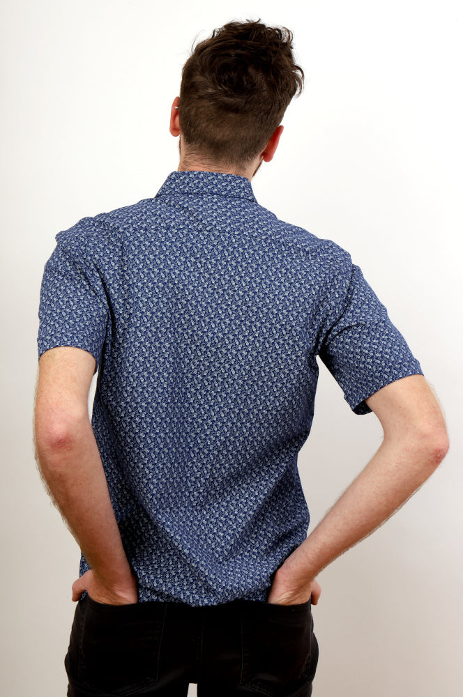BACK VIEW, MAN WITH HANDS IN BACK POCKETS, WEARING PAISLEY BLUE SHIRT