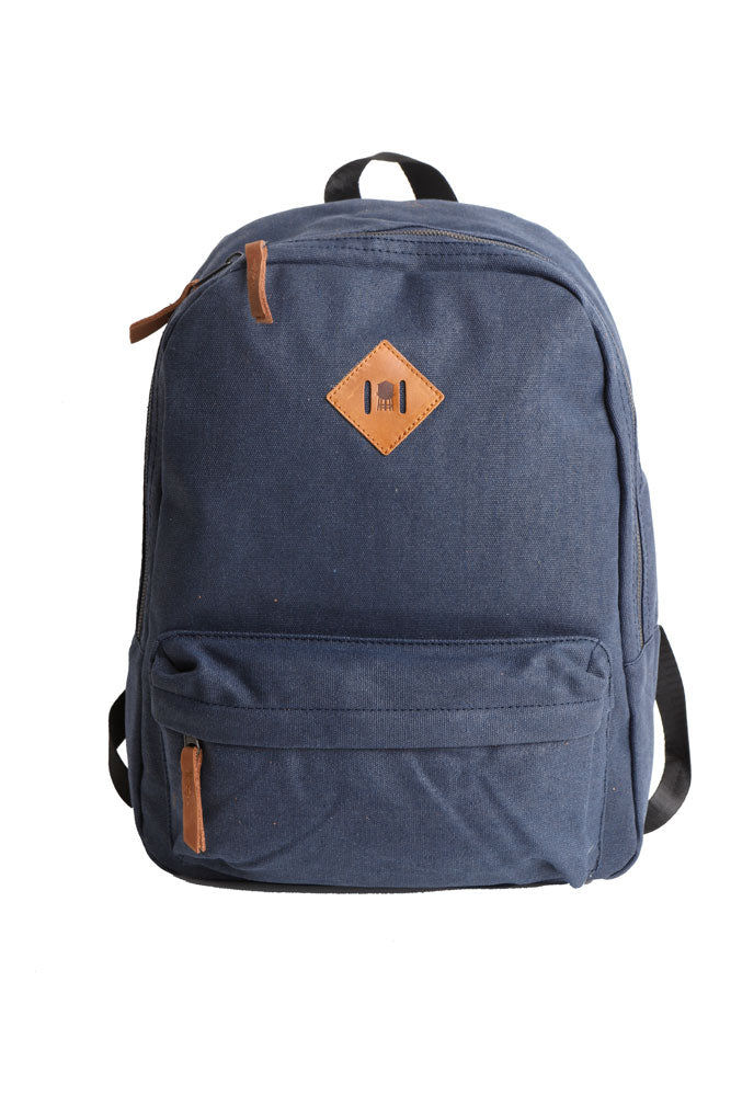 FRONT VIEW OF BLUE CANVAS BACKPACK WITH LEATHER PATCH