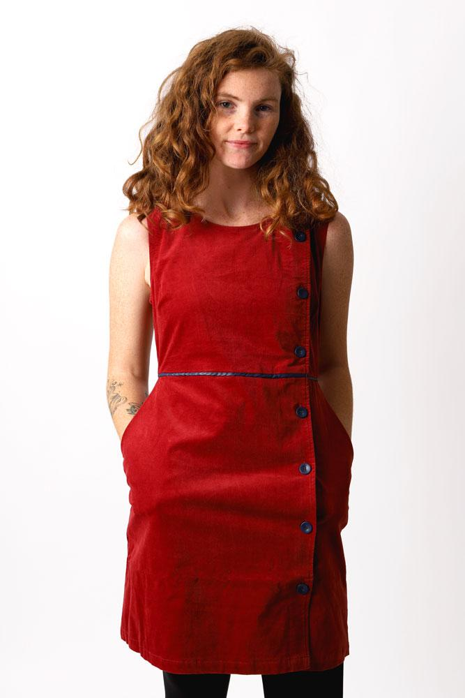 Curly haired women looks at camera in ruby dress with big buttons