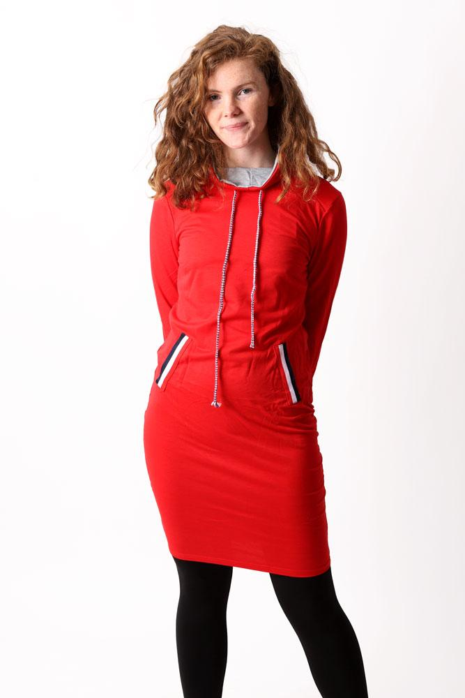 GIRL WEARS RED JUMPER DRESS WITH HANDS BEHIND HER BACK, AND BLACK FLEECE LEGGINGS ON