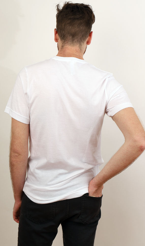 BACK VIEW OF A MAN WITH A WHITE TSHIRT ON AND HIS HAND IN HIS BACK RIGHT POCKET