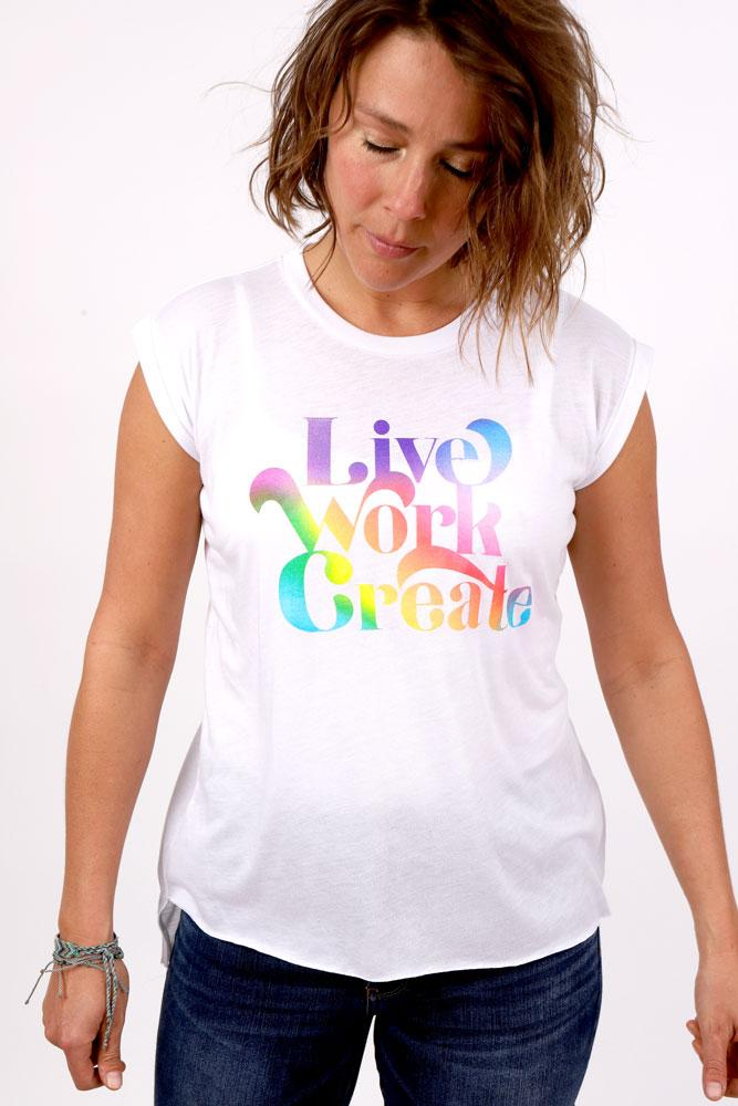 Women with eyes closed and head bowed towards the LIVE WORK CREATE graphic in rainbow on the chest of a light weight capped sleeve T