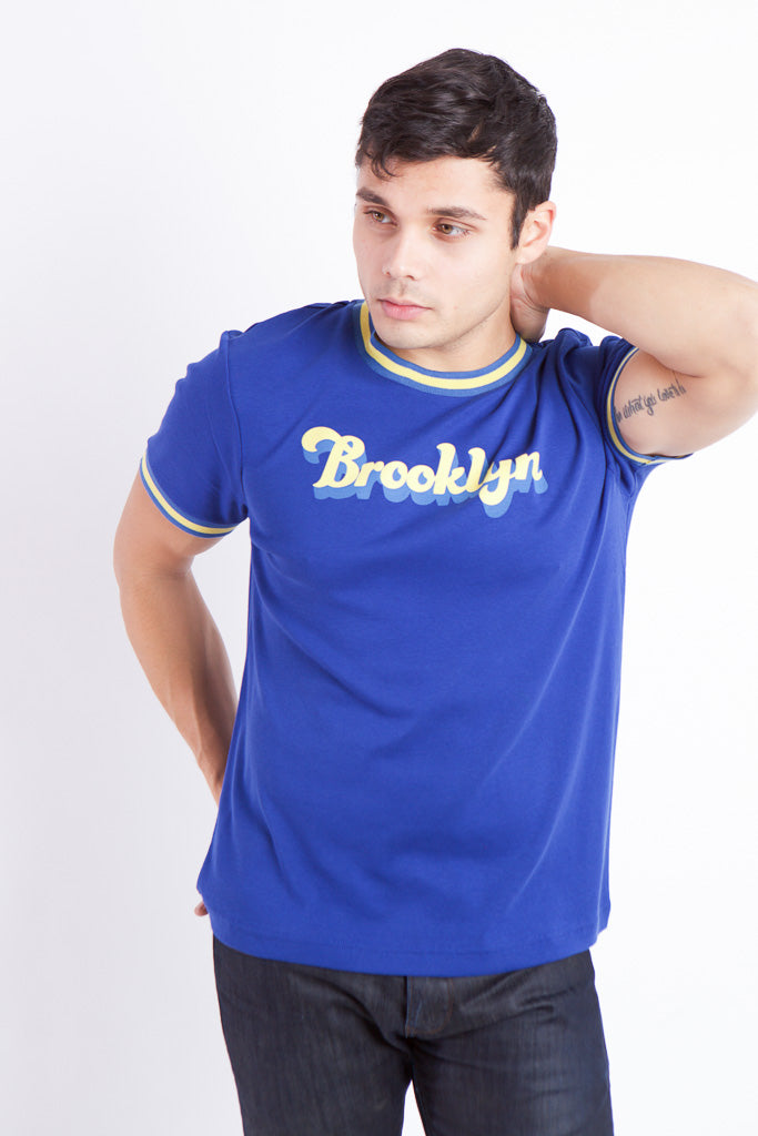MAN WITH ONE ARM BEHIND HEAD IN BLUE RIBBED T WITH YELLOW BANDING ON SLEEVES AND COLLAR, BROOKLYN TEXT ON CHEST IN YELLOW