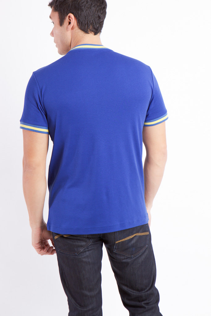 BACK VIEW OF MAN IN BLUE AND YELLOW RADICAL RIBBED KNIT SHIRT