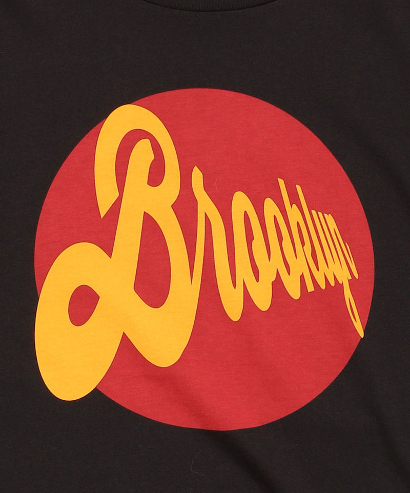 DETAIL OF BRIGHT ROUND GRAPHIC RED BACKGROUND AND BROOKLYN IN SCRIPT IN YELLOW MOUSTACHE TSHIRT