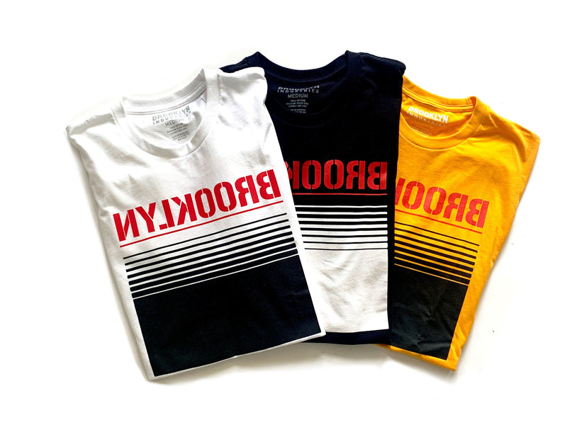 THREE OPTIONS OF  MINIMAL DESIGN T, BROOKLYN WRITTEN ON CONTRASTING COLORS. WHITE BLACK AND GOLD SHIRTS WITH RED AND BLACK DETAIL