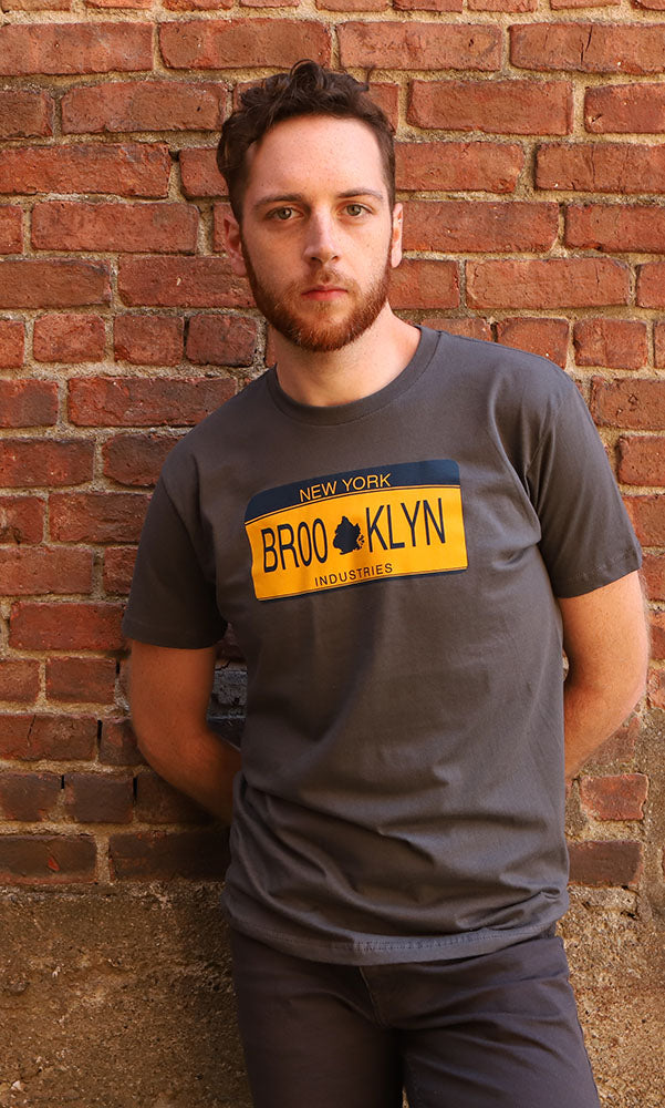 Man stands against a brick wall - grety shirt with a NYS license plate graphic with BROOKLYN in blue
