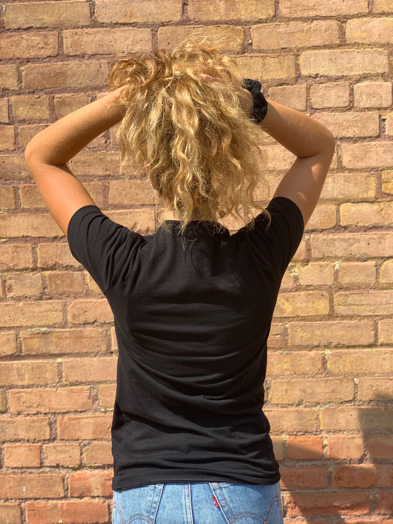 Back View of Black Neighboorhood Pint T with Women Holding up Curly Hair