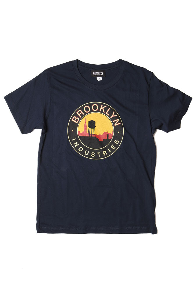 red and yellow sky against a black outline of city skyline and water tower brooklyn industries text surrounds the circle graphic, on a navy flat lay t-shirt