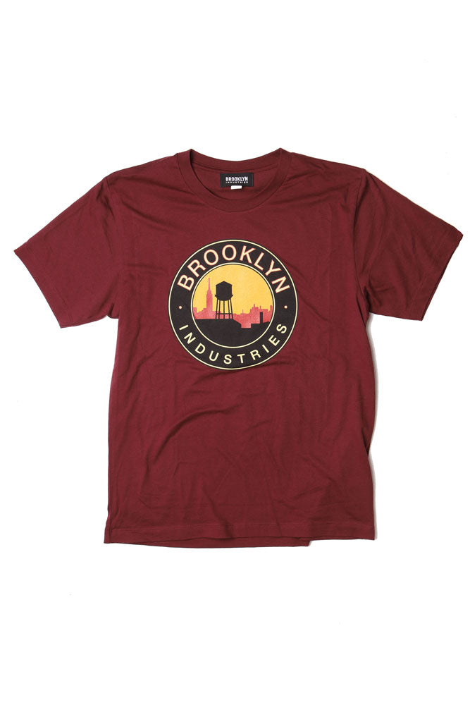 red and yellow sky against a black outline of city skyline and water tower brooklyn industries text surrounds the circle graphic, on a maroon flat lay tshirt
