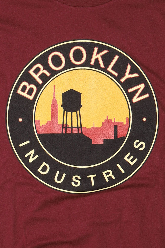 detail of red and yellow sky against a black outline of city skyline and water tower brooklyn industries text surrounds the circle graphic, on  maroon