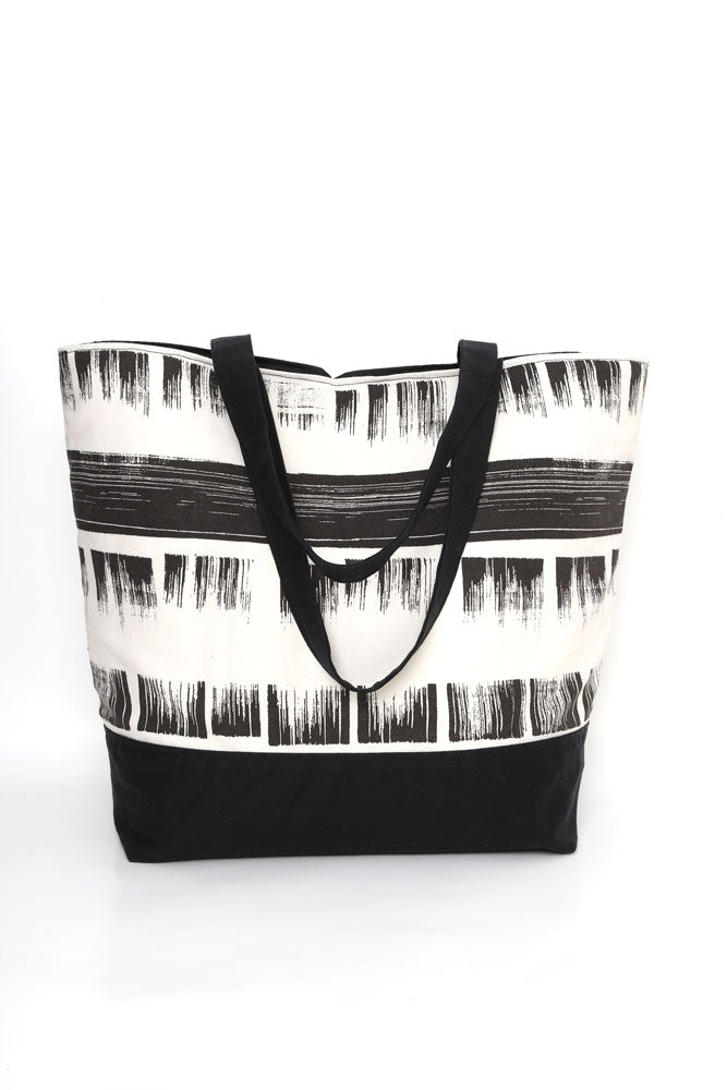 Large cotton canvas tote with waxed canvas handles and bottom.  black and white brushed textured pattern with black wax details,  back view with handles dropped down