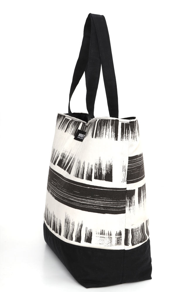 Large cotton canvas tote with waxed canvas handles and bottom.  black and white brushed textured pattern with black wax details,  side view