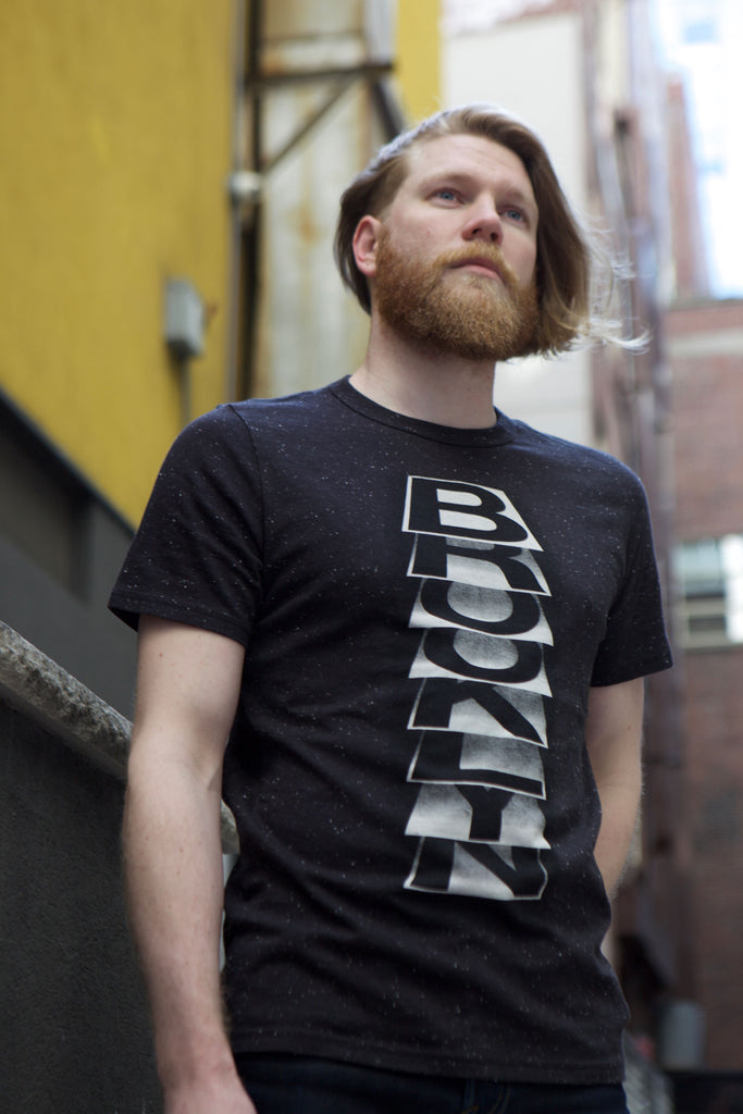 Man wearing eco black t-shirt with image of Brooklyn on each page of paper.