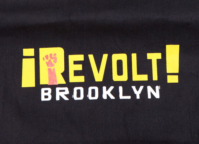 DETAIL OF BLACK CANVAS TOTE BACK WITH REVOLT BROOKLYN IN YELLOW AND WHITE TEXT