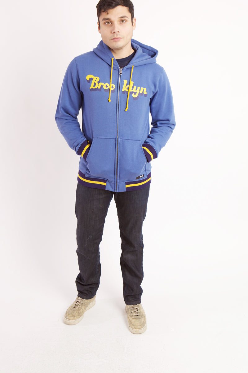 MAN WEARS SHOES, BLACK PANTS AND BLUE SWEATSHIRT WITH YELLOW BROOKLYN TEXT. HANDS IN POCKET OF SWEATSHIRT.