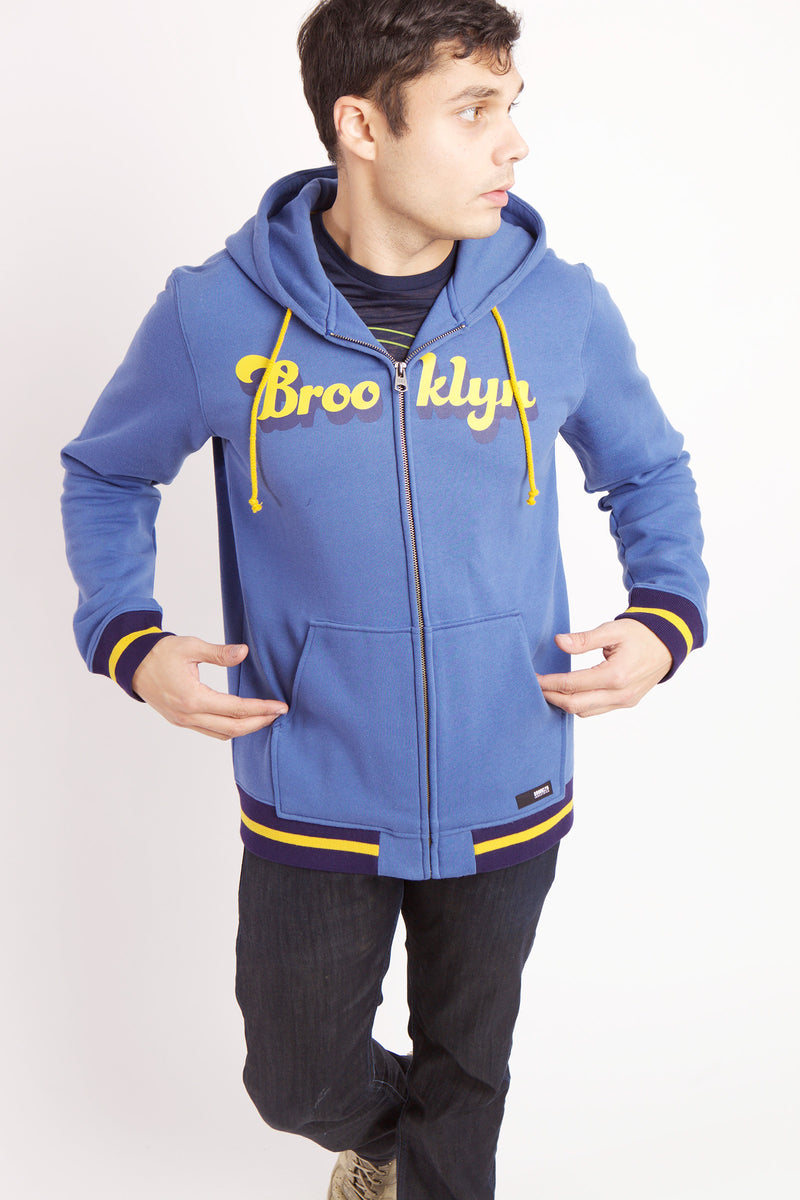 MAN PUTTING HANDS IN POCKET OF BLUE HOODED ZIP UP SWEATSHIRT WITH BROOKLYN TEXT ACROSS CHEST IN YELLOW