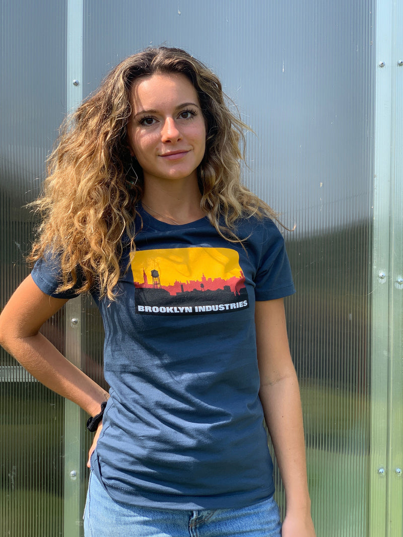 Smiling Women In Blue Brooklyn Industries Logo T in Jeans and Curly Hair