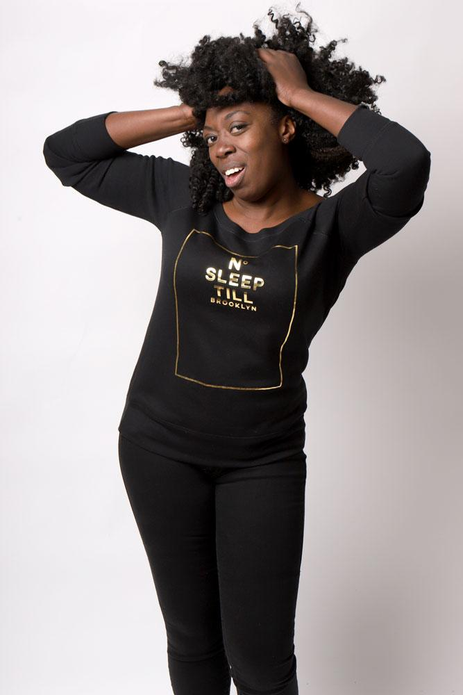 Women wears black pants and black scoop neck Sleep Number sweatshirt with hands up in her afro