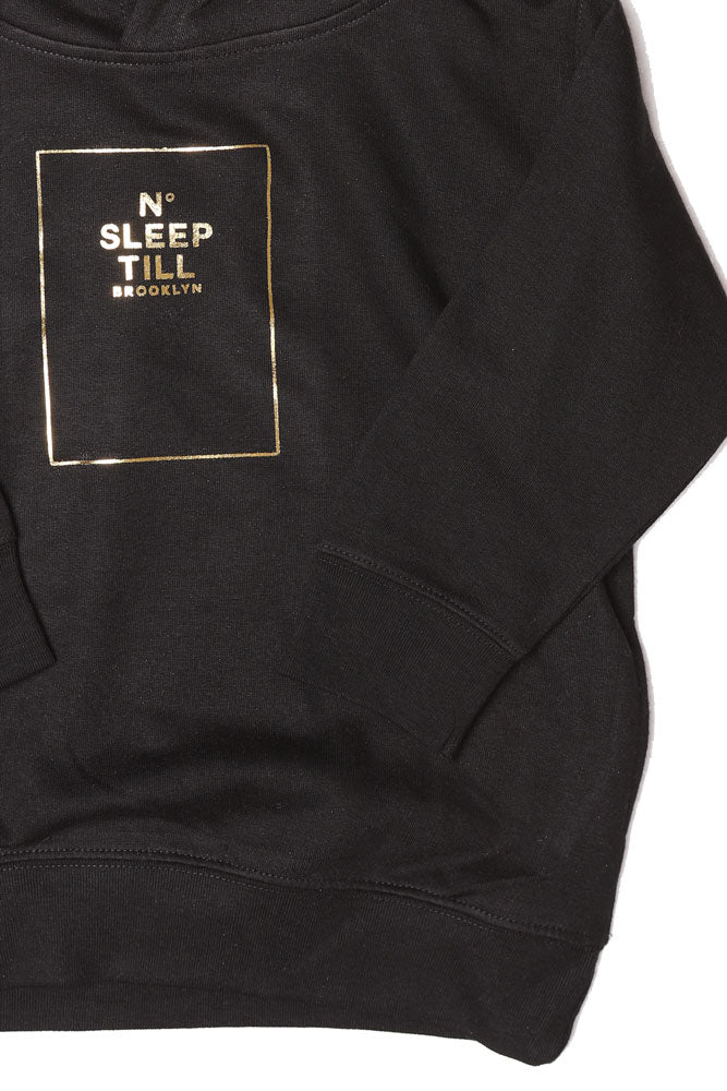 DETAIL OF TODDLER SIZED HOODED SWEATSHIRT WITH SLEEP NUMBER GRAPHIC IN GOLD. SWEATSHIRT IS BLACK
