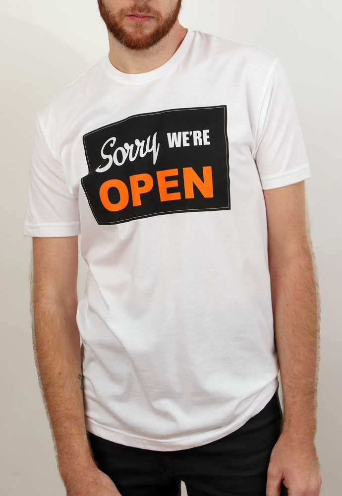 "man wears white tshirt with classic ""sorry we are open"" signage on chest"