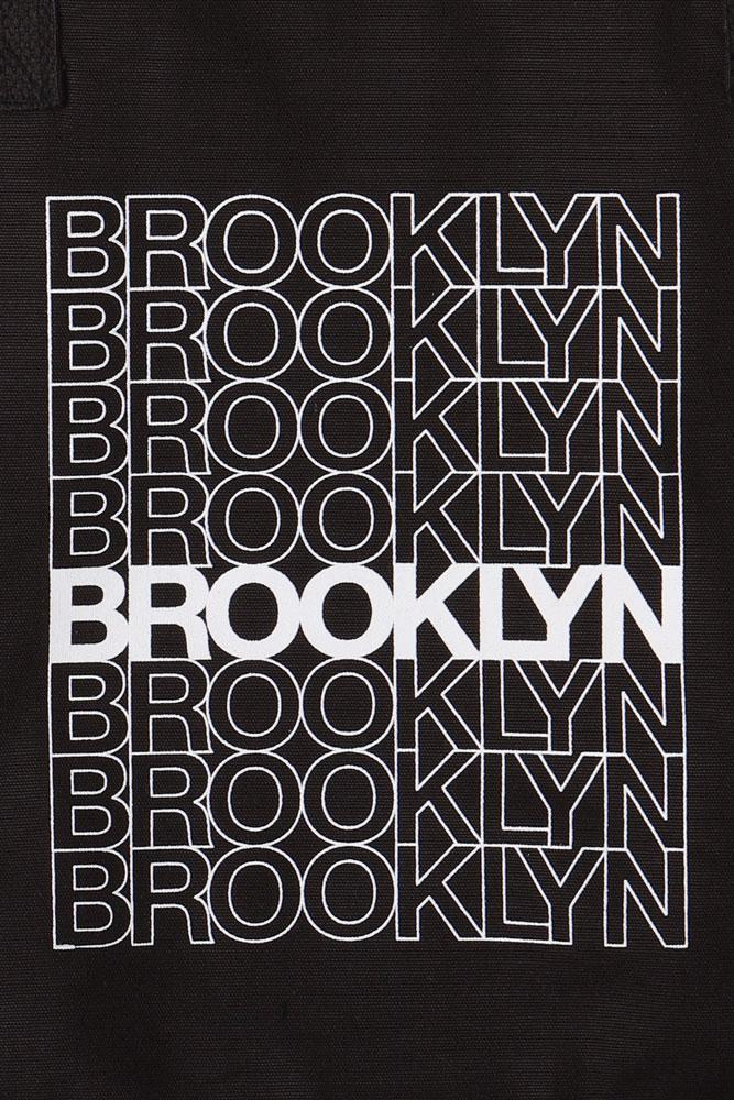 DETAIL OF ORGANIC COTTON TOTE BAG WITH BROOKLYN TEXT DOWN THE FRONT LIKE A CLASSIC BODEGA BAG - BLACK WITH WHITE GRAPHIC