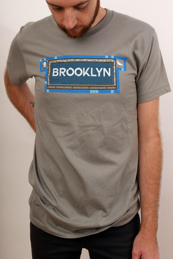 grey shirt, word Brooklyn is depicted in subway tile mosaic