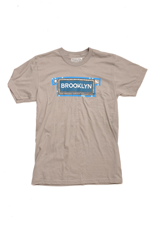 FLAT LAY OF CHARCOAL COLORED TSHIRT WITH SUBWAY TILE SPELLING BROOKLYN IN BLUE TONES