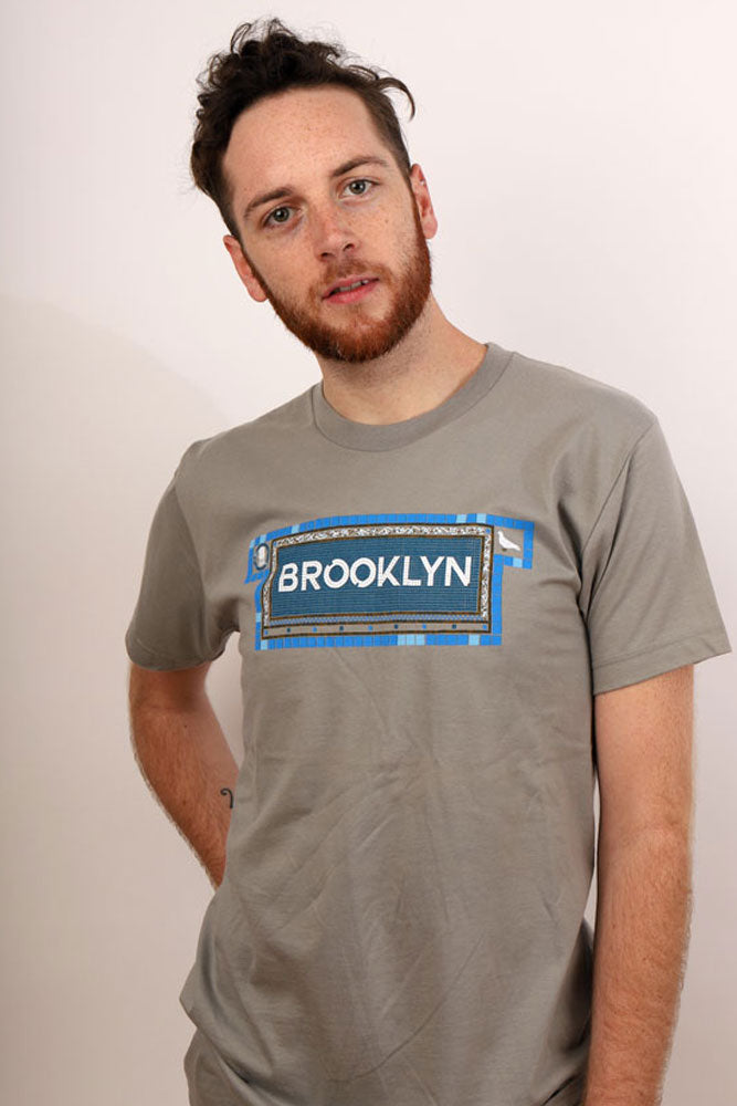Man looks past camera in grey shirt, word Brooklyn is depicted in subway tile mosaic