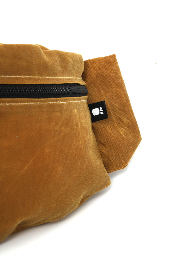 DETAIL VIEW OF ZEKI WAISTPACK IN TOAST WAX CANVAS WATER TOWER TAG ON THE SIDE