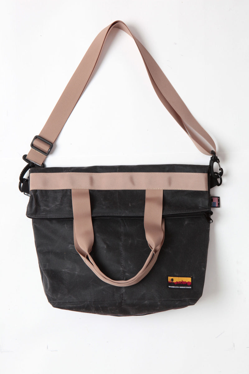 Waxed zip messenger bag in coal wax with tan handles and straps.