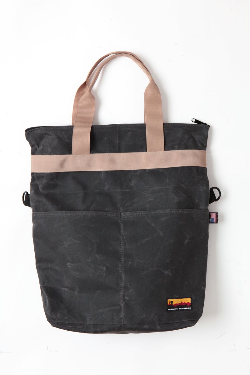 Waxed zip messenger bag open in black wax with tan handles and straps.