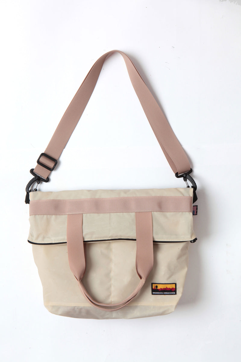 Waxed zip messenger bag in natural wax with tan handles and straps.