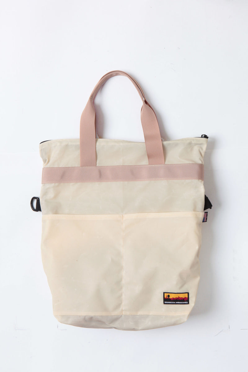 Waxed zip messenger bag open in natural wax with tan handles and straps.