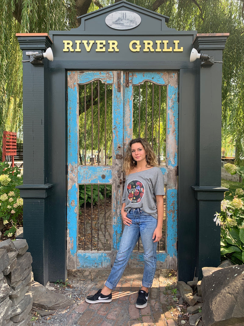 women in jeans stands at river grill gate, one hand in pocket, grey off shoulder shirt with circle of flowers on front with text of we grow hard, and Brooklyn intersecting it