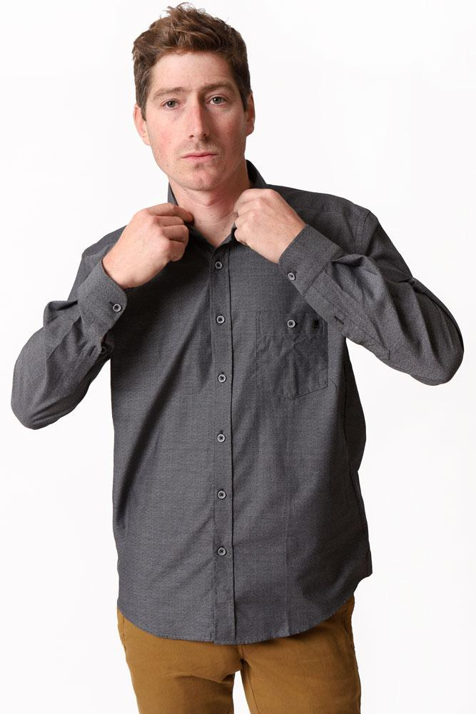 man fixes collar in grey button up shirt and toast pants